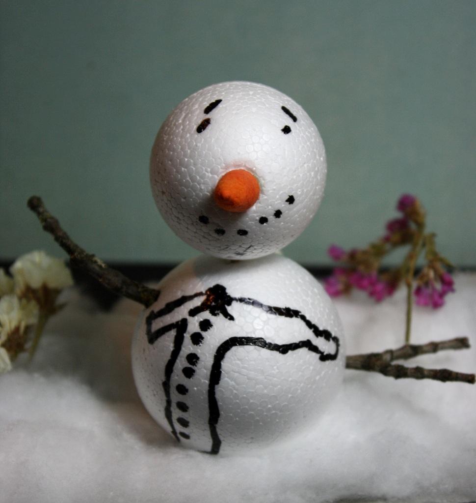 ein gebastelter Schneemann im Garten mit Astarmen und aufgemaltem T-Shirt