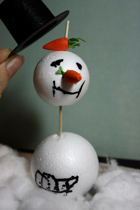 gebastelter Schneemann, der eine Möhre unter dem Hut versteckt