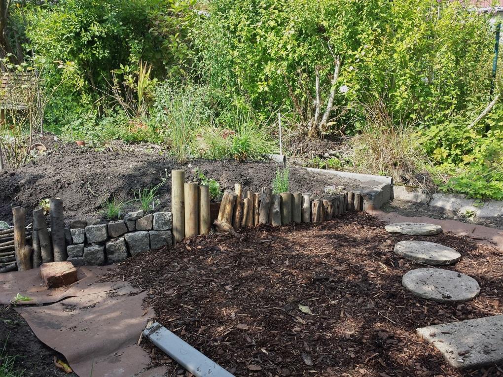 Hochbeetumrandung aus wiederverwerteten Pflastersteinen und Totholz